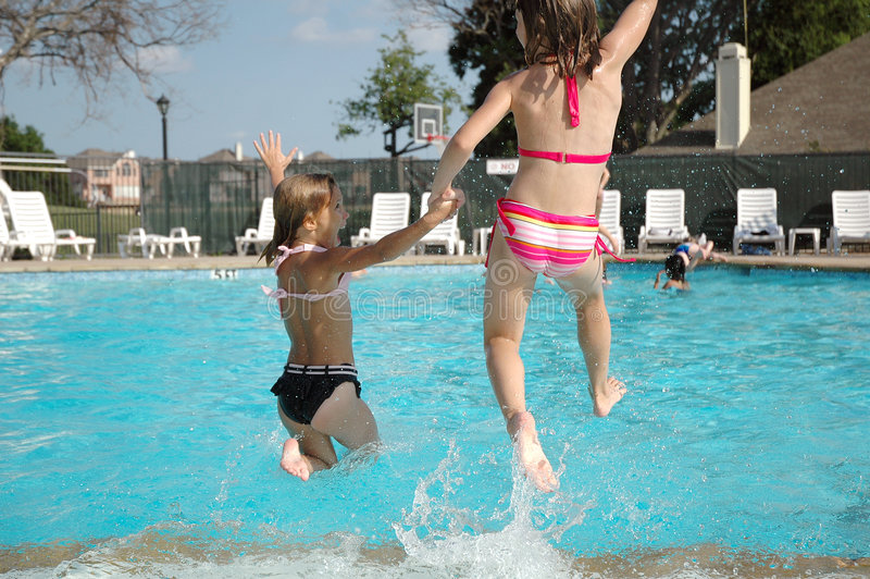 Jumping together. Two friends hold hands and jump into the pool together. Summer is here and school is out stock image