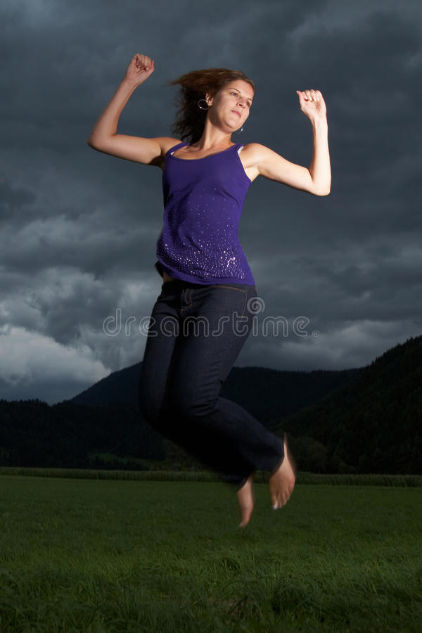 Jumping through the tough times. Young woman jumping under a dark sky before a thunderstorm. Slight motion bluriness on feet intended to show the motion royalty free stock photography