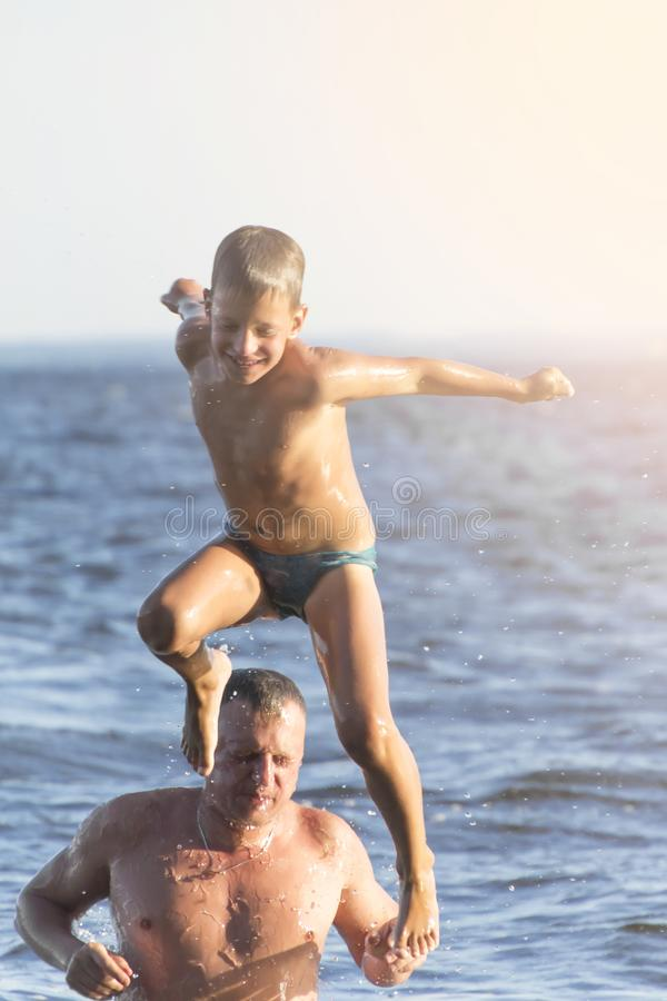 Jumping in the water. Man and boy are having fun and splashing in the water. Summer holiday concept. Toned. Father and son are having fun and splashing in the stock photo