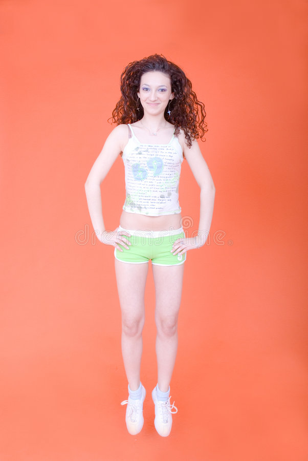 Jumping Woman. Young woman with curly dark hair, jumping and bouncing, wearing shorts and tank-top stock image