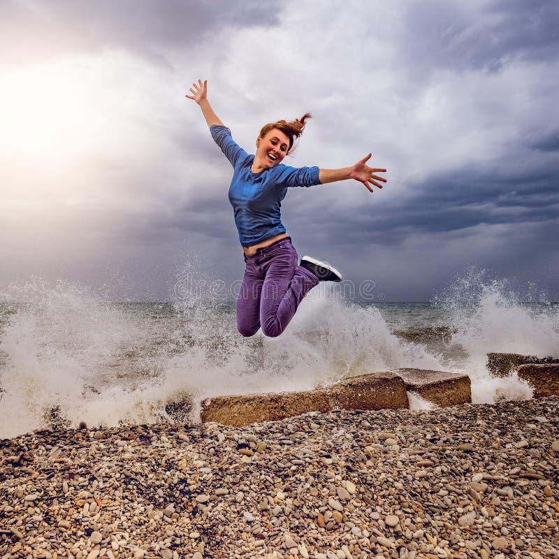 Jumping woman on the sea coast. stock photo