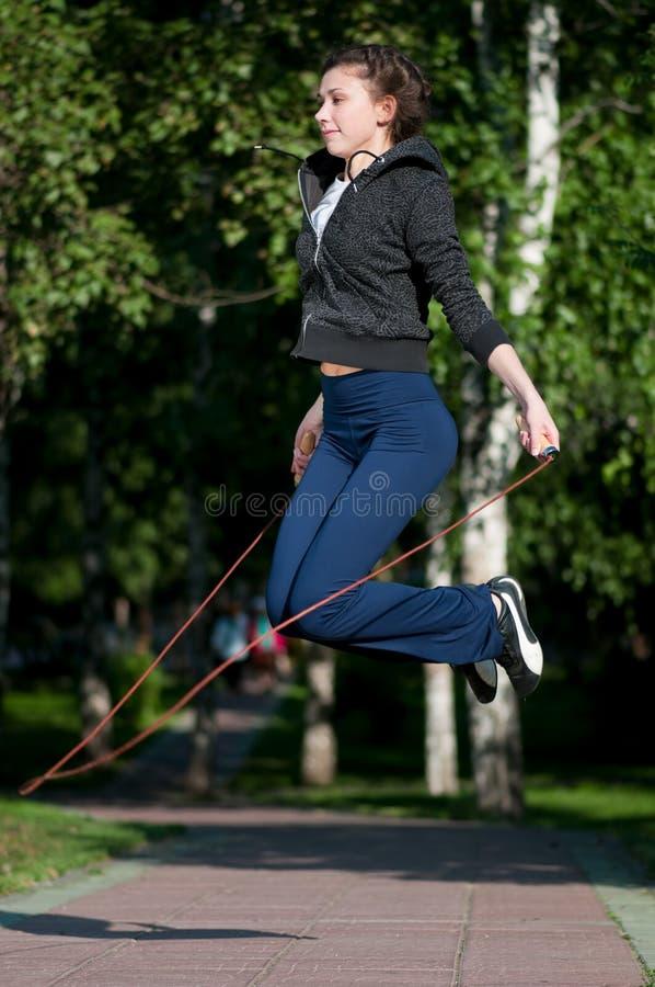 Jumping woman with skipping rope at park. Beautiful young woman doing exercise with skipping rope at park. Jumping stock photos