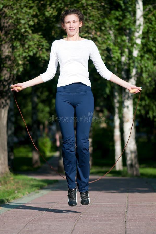 Jumping woman with skipping rope at park. Beautiful young woman doing exercise with skipping rope at park. Jumping royalty free stock photos
