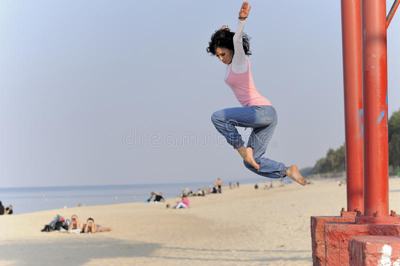 Jumping young girl on beach stock photos
