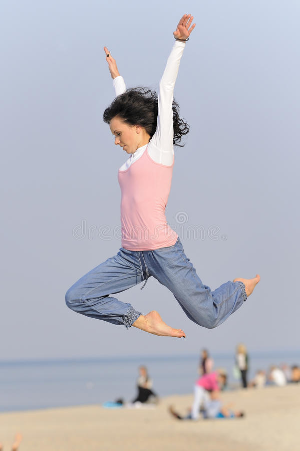 Jumping young girl on beach royalty free stock image
