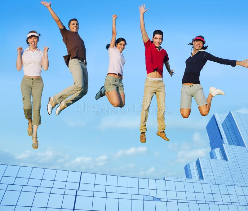 Jumping young people group on city buildings. Jumping young people happy group over city buildings cityscape stock image