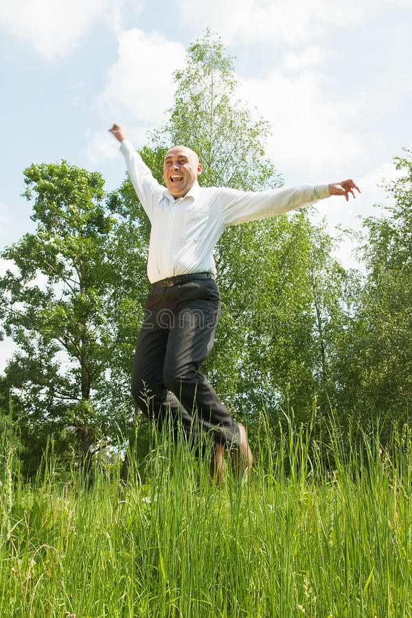 Download Jumping Young Smiling Men Against Summer Meadow Stock Photo - Image: 14644920