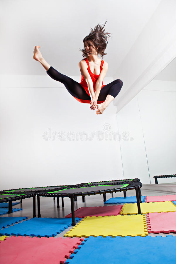Jumping young woman on a trampoline stock photography