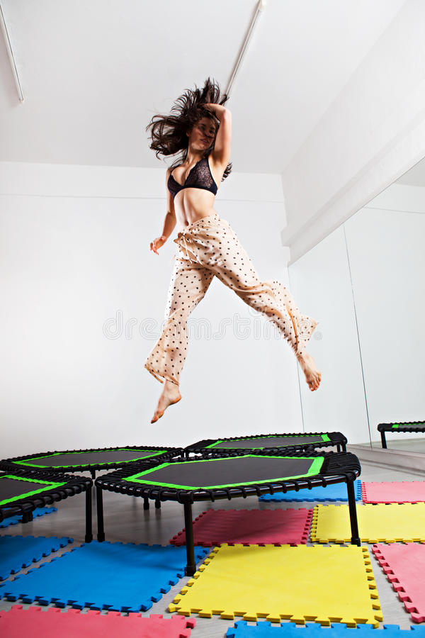 Jumping young woman on a trampoline stock photos
