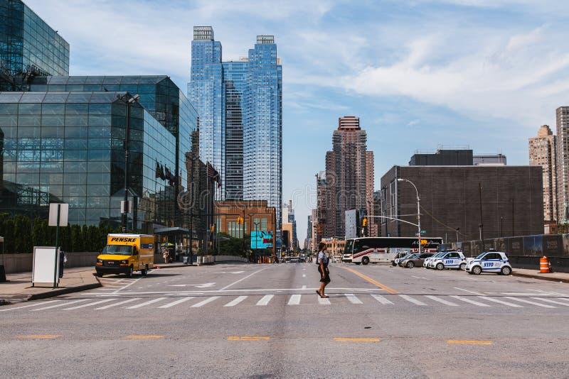 Jun 22, 2017 A kobieta krzyżuje 11 aleję w środku miasta Manhattan, obrazy stock
