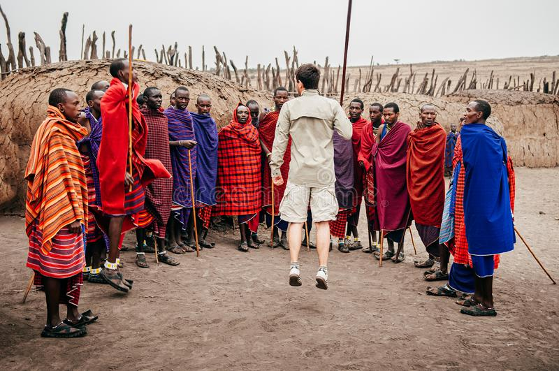 Group Masai or Maasai tribe peoples in red cloth and European tourist jumping by clay hut. Ethnic group of Ngorongoro Consevation royalty free stock photos