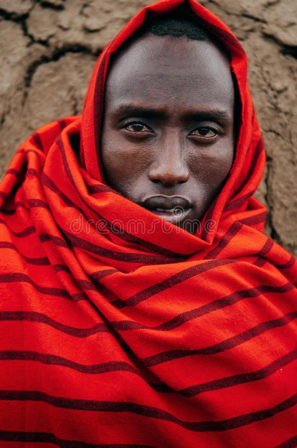 Masai or Maasai tribe man in red cloth portrait eyes staring at camera. Ethnic group of Ngorongoro Consevation, Serengeti in. JUN 24, 2011 Serengeti, Tanzania stock image