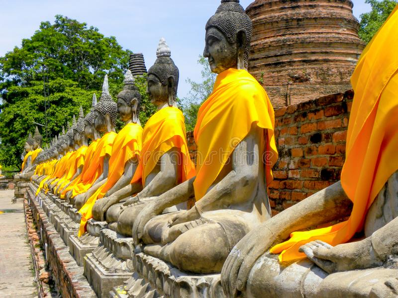 June 2011 Ayutthaya, Thailand - Buddhist temple with yellow cloth adorning the staues. stock photography
