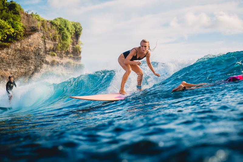 June 22, 2018. Bali, Indonesia. Surf girl ride on surfboard. Surfers in ocean during surfing stock image