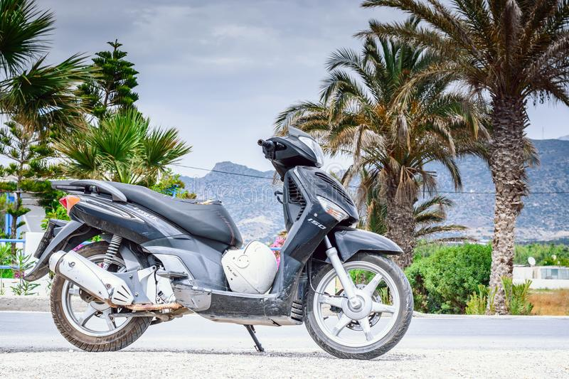 June 7, 2017, the island of Crete, Greece. Black scooter on the side of the road on the background of palm trees and mountains. stock image