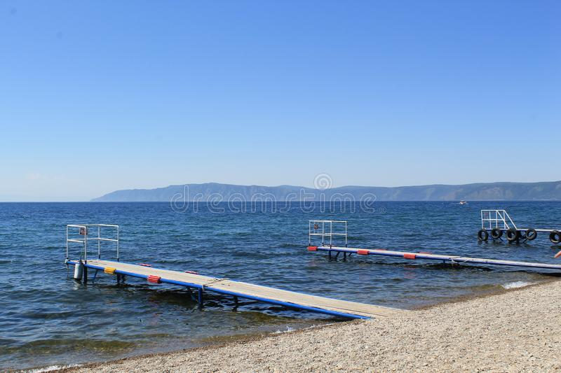 Pier on Lake Baikal. June in Listvyanka village, piers on the shore of Lake Baikal, clear sky, clear water stock photography