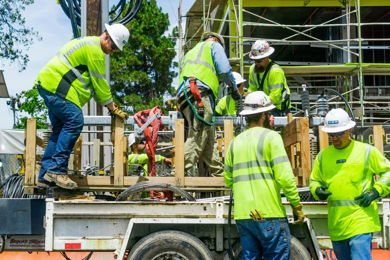 June 24, 2019 Mountain View / CA / USA - Team of construction workers wearing bright yellow vests and hard hats stock photo