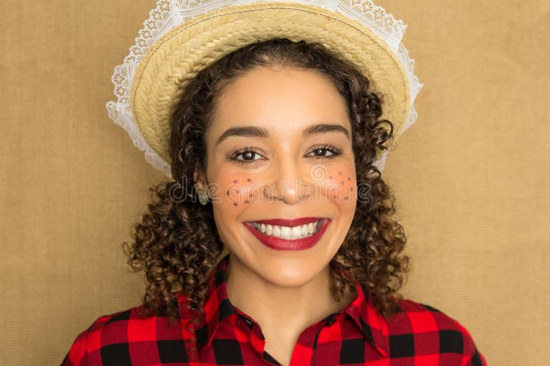 June Party is Festa Junina in Brazil. Pretty woman is having a big smile and looking at the camera. She wears red and black plaid stock image