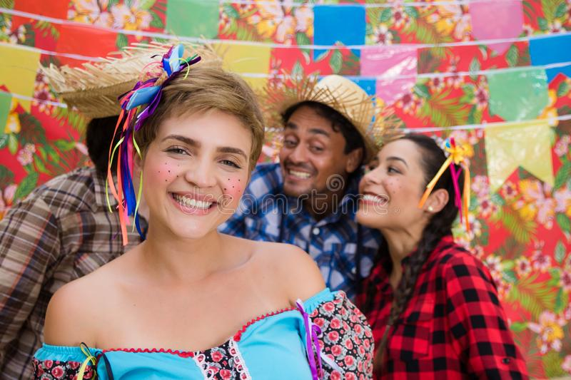 June Party: Festa Junina. People in traditional plaid clothes at holiday festival. Decoration of flags in background stock photography