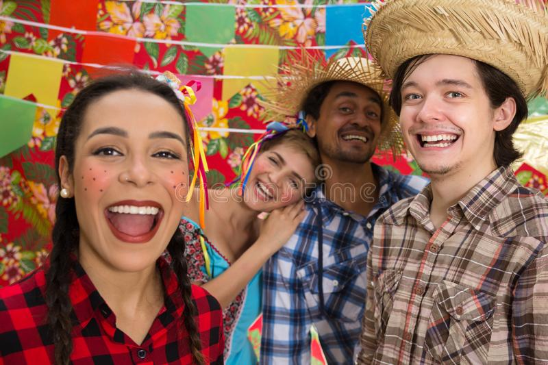 June Party: Festa Junina. People in traditional plaid clothes at holiday festival. Decoration of flags in background royalty free stock image