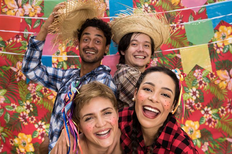 June Party: Festa Junina. People in traditional plaid clothes at holiday festival. Decoration of flags in background stock image