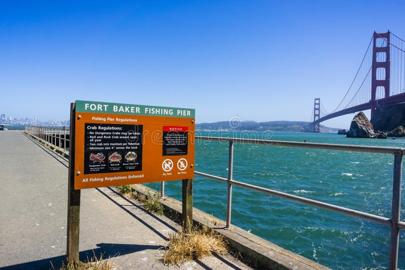 June 29, 2018 Sausalito / CA / USA - Fort Baker Fishing Pier posted regulations regarding crab fishing; Golden Gate Bridge visible stock photos