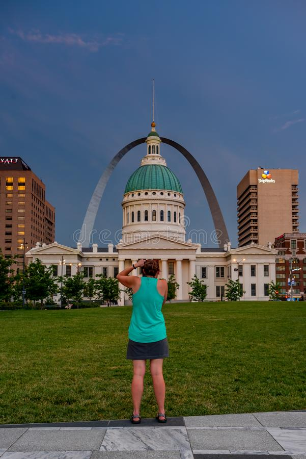 Woman Takes Photograph of St. Louis Arch. June 11, 2018: St. Louis, United States: Woman Takes Photograph of St. Louis Arch and Old Courthouse royalty free stock photography