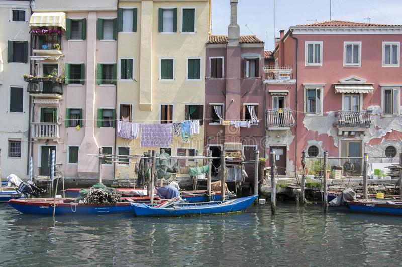 June 15, 2017 Sunny day in Chioggia, way of living in houses by the water, fishing housing in block of flats with fishing boats stock photography