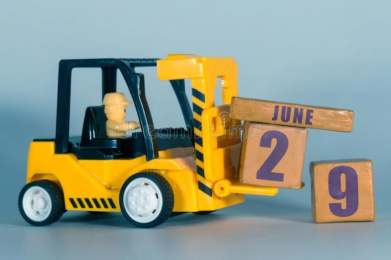 June 29th. Day 29 of month, Construction or warehouse calendar. Yellow toy forklift load wood cubes with date. Work planning and. Time management. summer month stock photo