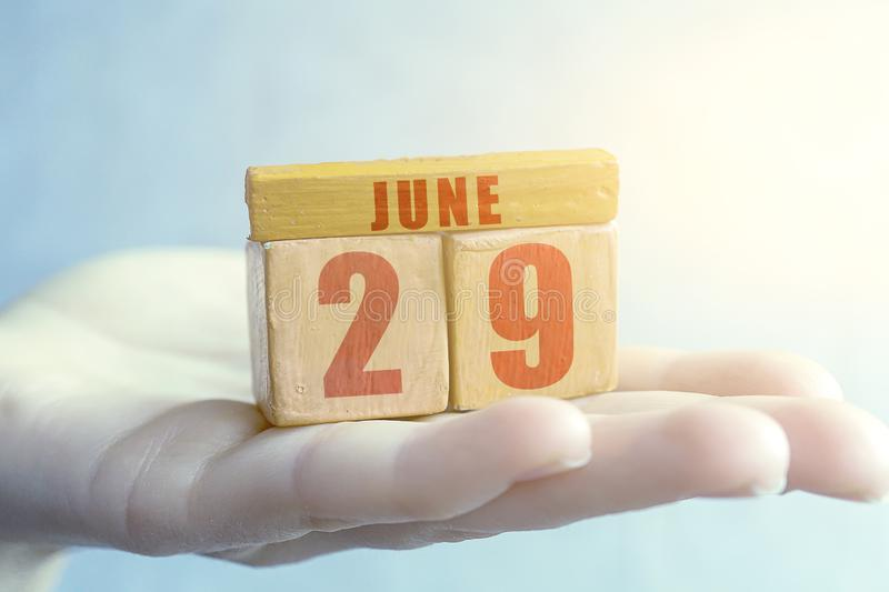 June 29th. Day 29 of month,Handmade wood cube with date month and day on female palm summer month, day of the year concept. June 29th. Day 29 of month, Handmade royalty free stock image