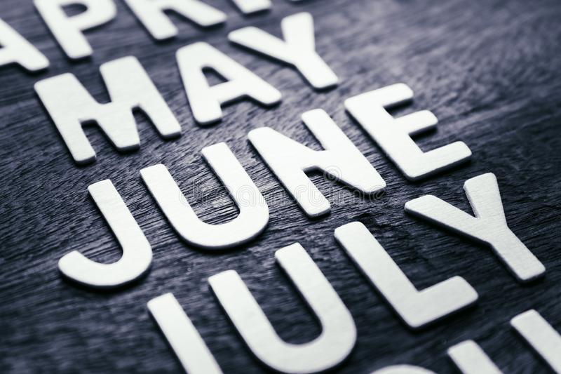 June Wood Letters. Closeup wood letters of June in running name of month royalty free stock photos