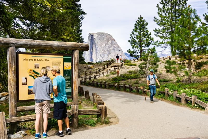 June 27, 2019 Yosemite National Park / CA / USA - Unidentified people visiting Glacier Point; Half Dome visible in the background royalty free stock images