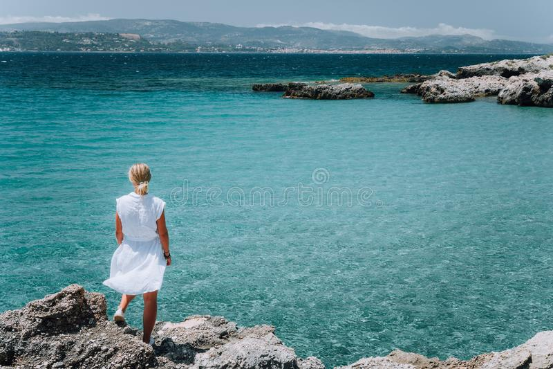 Jung adult women in white dress on summer vacation in front of sea coast landscape of small beach with crystal clear royalty free stock photo