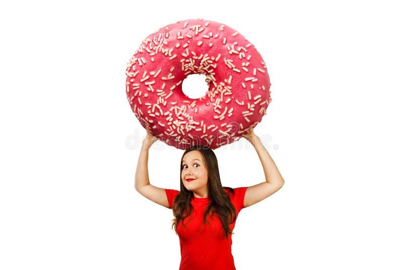 Jung süßes, lustiges Mädchen hält sich vor ihrem riesigen Donut, isoliert auf einem weißen Hintergrund lizenzfreies stockbild