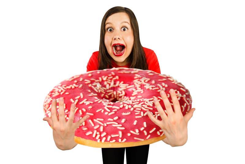 Jung süßes, lustiges Mädchen hält sich vor ihrem riesigen Donut, isoliert auf einem weißen Hintergrund stockfoto