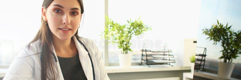 Junge Ärztin benutzt Computer an Arbeitsplatz lizenzfreie stockfotos