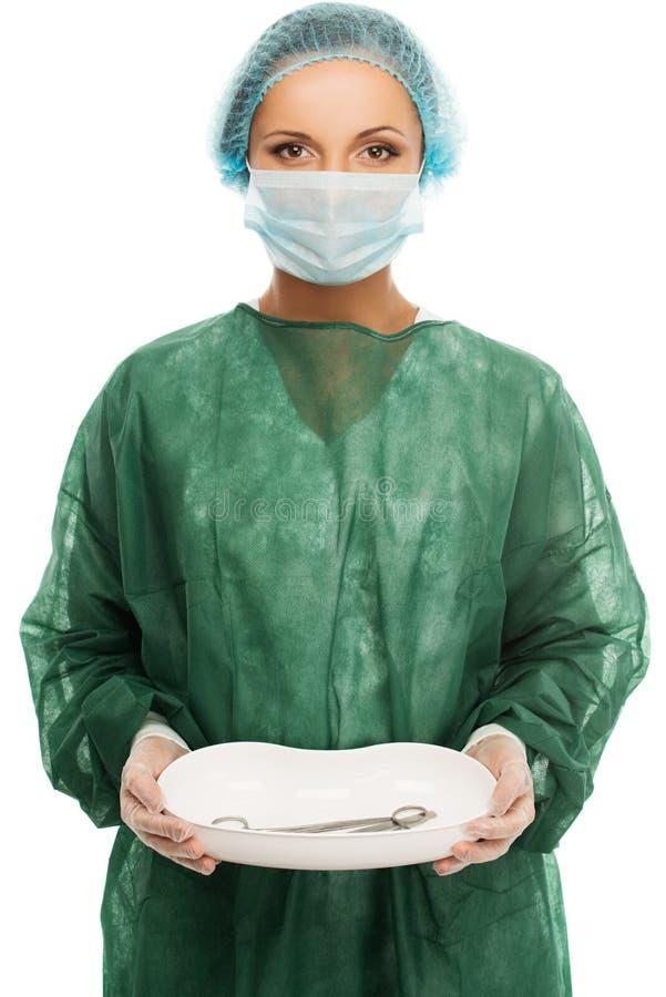 Junge Ärztin in der Kappe und in der Gesichtsmaske stockbild