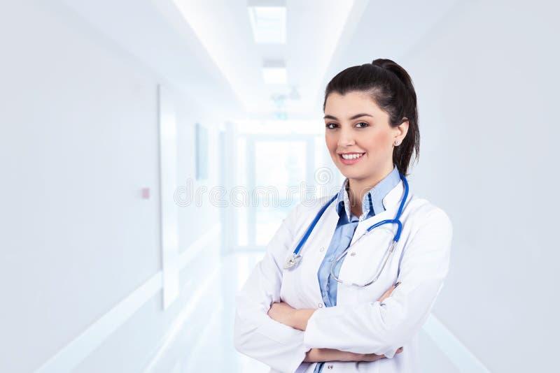 Junge Ärztin, die auf Krankenhaus steht und lächelt stockfoto