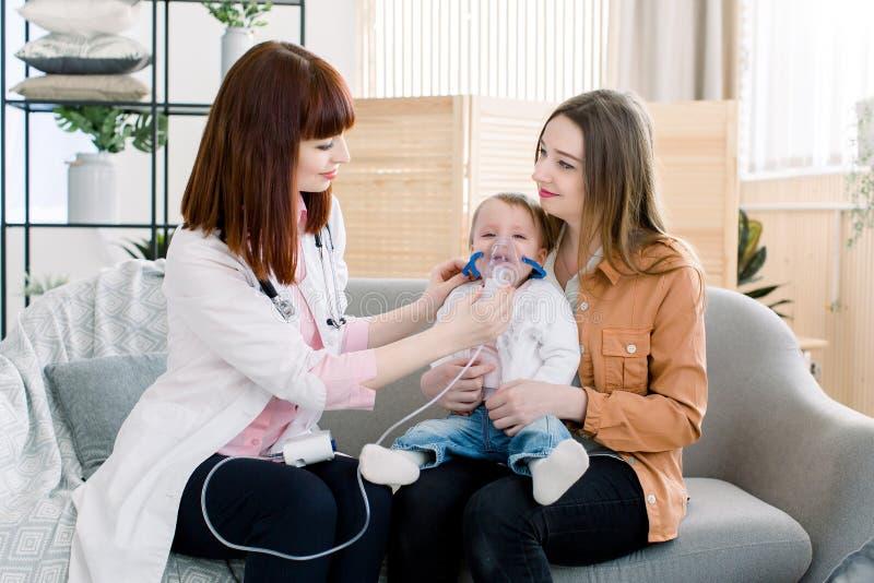 Junge Ärztin, die zu wenigem Baby mit der Zerstäubermaske, zeigend hilft, wie man Inhalationstherapie für sie macht stockfotos