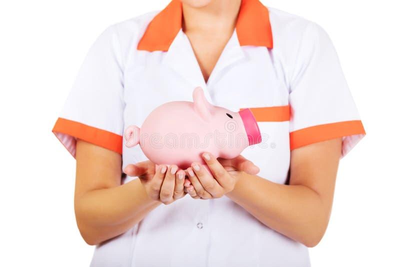 Junge Ärztin oder Krankenschwester, die ein piggybank halten lizenzfreies stockfoto
