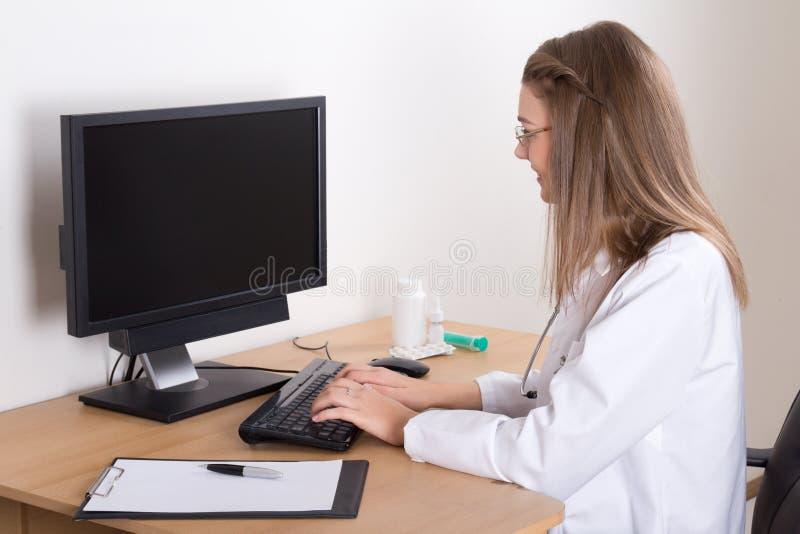 Junge Ärztin unter Verwendung des Computers im Büro lizenzfreie stockbilder