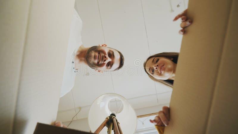 Junge Öffnungspappschachtel des glücklichen Paars und Schauen inner und Schließen es überprüfend nach Verlegung im neuen Haus lizenzfreies stockbild