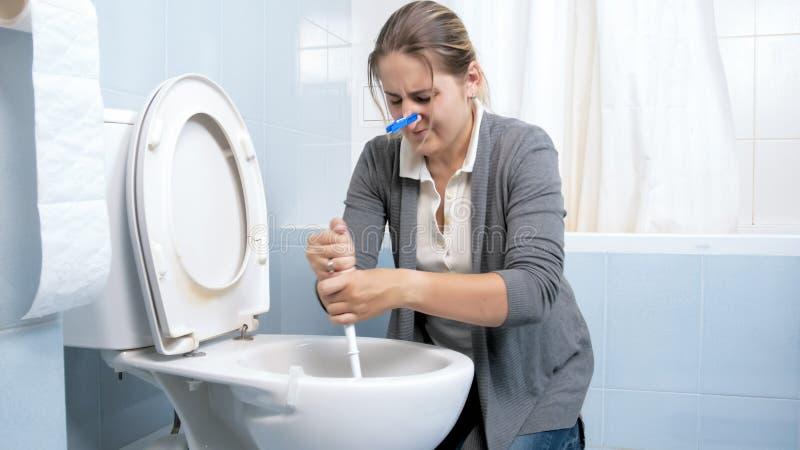 Junge überempfindliche Hausfrau, die schmutzige Toilette mit Bürste säubert stockfotografie