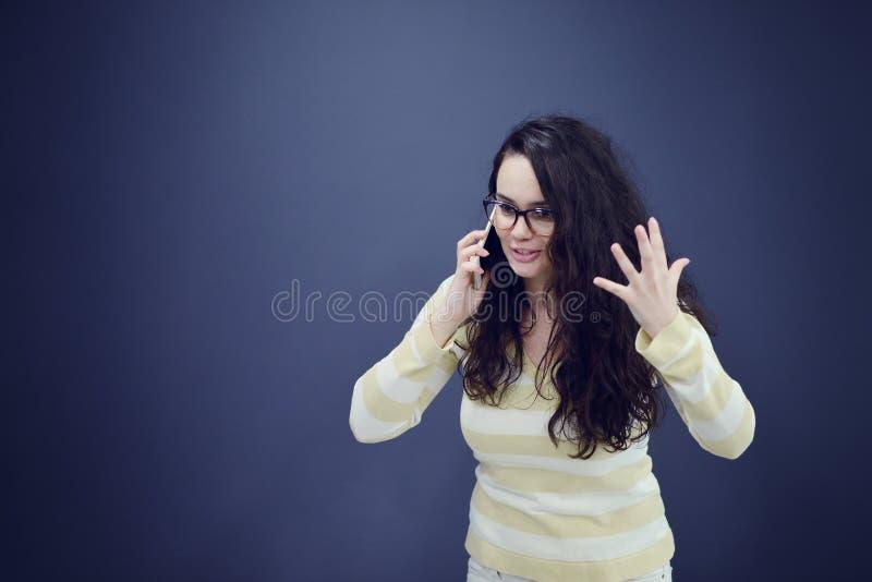 Junge, überzeugte, erfolgreiche und schöne Geschäftsfrau mit dem Handy lokalisiert lizenzfreie stockbilder