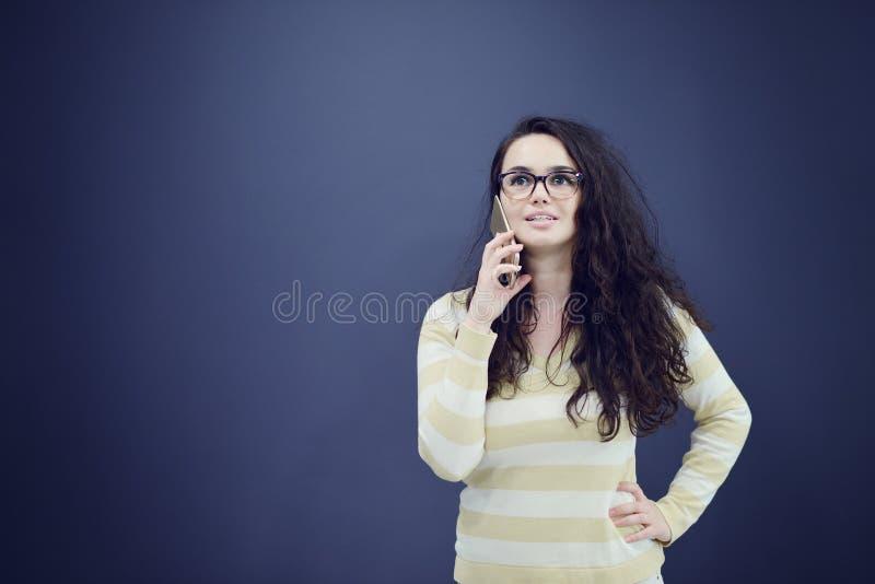 Junge, überzeugte, erfolgreiche und schöne Geschäftsfrau mit dem Handy lokalisiert lizenzfreie stockfotos