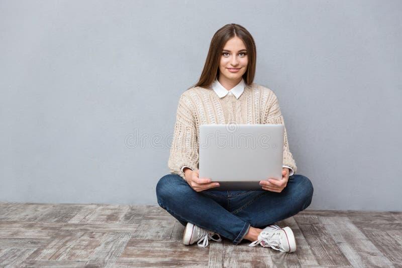 Junge überzeugte Frau, die Laptop sittin auf Bretterboden verwendet stockfotos