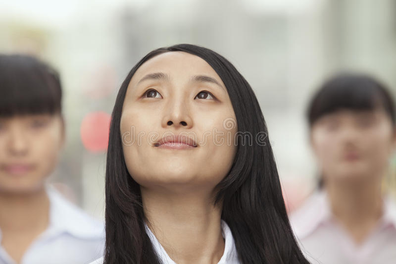 Junge überzeugte Geschäftsfrau Looking oben, draußen mit Leuten im Hintergrund stockfotografie