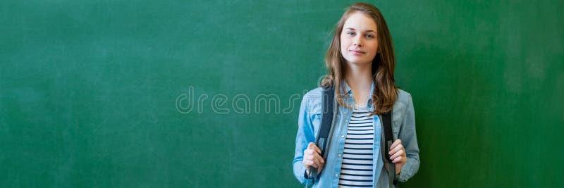 Junge überzeugte lächelnde weibliche hohe Schülerstellung vor Tafel im Klassenzimmer, einen Rucksack tragend stockbild