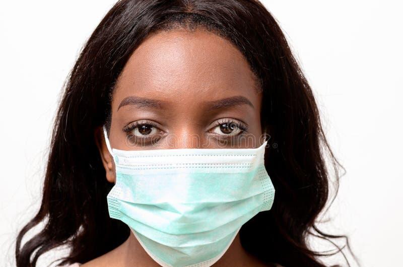 Junge Afrikanerin, die eine chirurgische Gesichtsmaske trägt stockfotografie