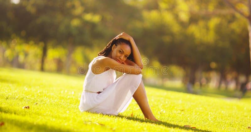 Junge Afrikanerin, die in einem Park sitzt stockfotografie